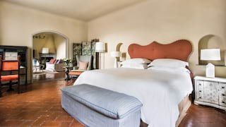 Spacious light and airy hotel room with a terracotta-tiled floor and vast pillowy bed