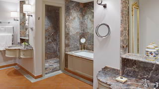 Vast marble-tiled bathroom with opulent 'his and hers' sinks and an enclosed shower