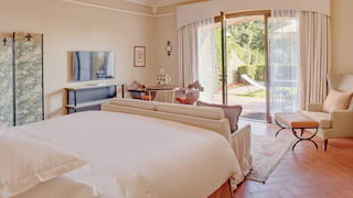 Spacious and light hotel room with open patio doors leading to a garden terrace