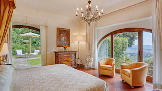 Spacious hotel room with a large arched window and lemon yellow accents