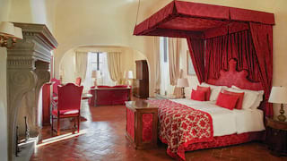Vast hotel suite with a red-patterned satin four-poster bed and grand stone fireplace