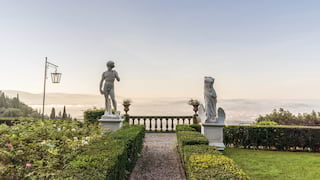 'David' and 'Venus de Milo' statues at the end of a garden path lined by a small hedge