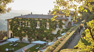 Bougainvillea covered hotel surrounded by lawns in tiered gardens at sunset