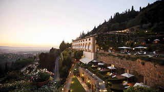 Hilltop monastery with tiered lamplit gardens and views of sunset over Florence