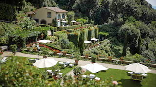 Gorgeous tiered hilltop gardens with sunbeds and parasols on manicured lawns