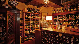 Lamplit wine cellar lined with vintage wine bottles and a wood beamed ceiling