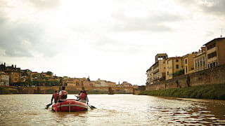 Three people in red life jackets paddling a raft down a river in the centre of Florence