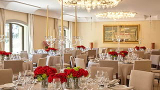 Stylish event room with modern chandeliers, dotted with circular wedding tables