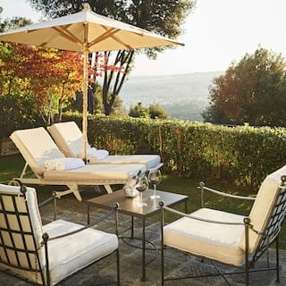 Wine glasses on a patio table beside two sunbeds under a parasol on a hilltop terrace