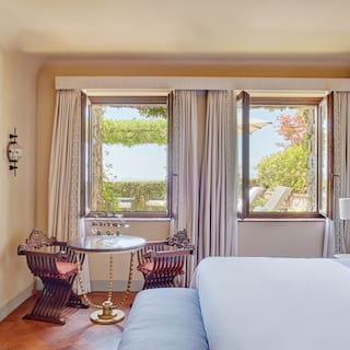 Light and airy hotel room with double windows and terracotta-tiled floor