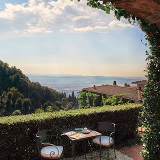 View through an ivy-coated stone arch of a breakfast terrace overlooking Florence