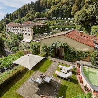 Aerial view of a hotel suite garden patio with a plunge pool and sunbeds on a hilltop