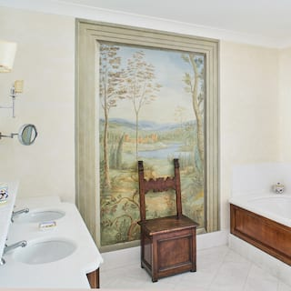 Spacious hotel bathroom with 'his and hers' sinks and a Michelangelo-style wall mural