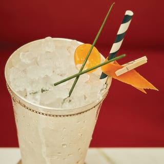 Close-up of a mint julep cocktail topped with crushed ice and garnished with chives