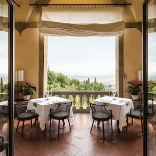 Circular domed restaurant terrace with linen-topped tables with hilltop views of Fiesole
