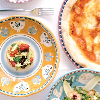 Birds-eye-view of brightly-patterned circular dishes topped with salads and pizza