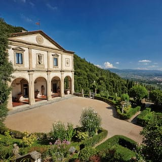 Classical exterior of a former Italian monastery with arched cloisters and a grand drive