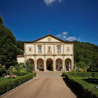 Classical facade of a former monastery with arched cloisters and Corinthian columns