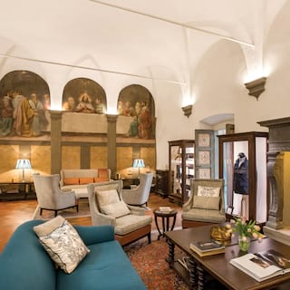 Double-height barrel-vaulted room with medieval styling and a mural of the last supper