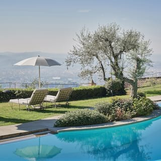 Mirror-still hilltop outdoor pool surrounded by a lawn with views across Florence