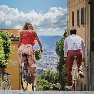 Lady and a man on bicycles on a cobbled Florentine street beside a classic Fiat car