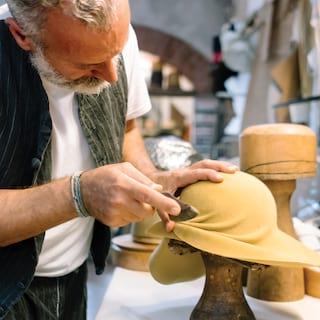 Close-up of milliner Antonio Gatto preparing a lemon-coloured lady's hat