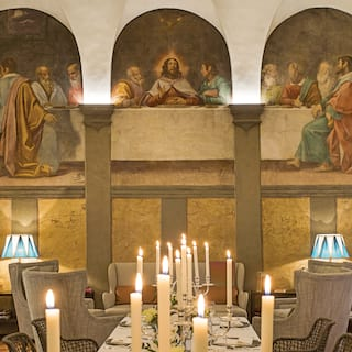 Candlelit banquet table in a barrel-vaulted room with a wall mural of the last supper