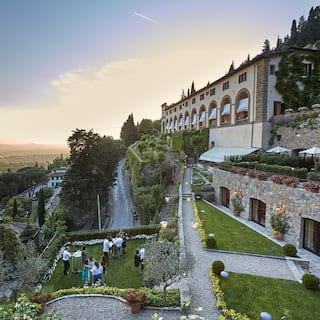Aerial view of guests celebrating in stunning hilltop gardens at sunset