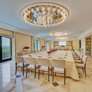 Large banquet table set for a meeting in a marble-tiled bright and airy room
