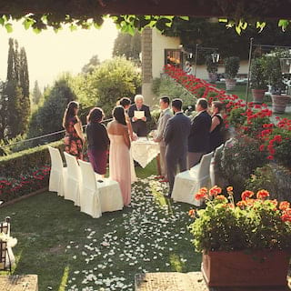 Guests standing at an intimate wedding ceremony in a garden coated with rose petals