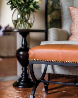 Close-up of a brass studded tan leather footstool next to a flower vase on a side table