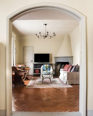 Light and airy hotel suite with polished parquet floors and an archway to a lounge area