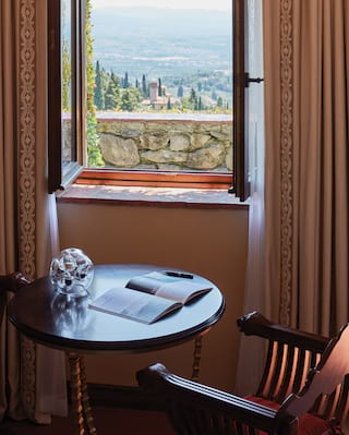 Open window with views over a stone wall of the hills of Fiesole dotted with trees
