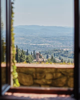 View through an open window of the hills of Fiesole dotted with cypress trees