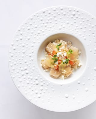 Birds-eye-view of a ravioli dish topped with parmesan in a wide-brimmed white bowl