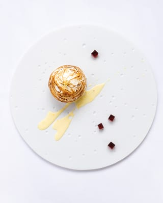 Birds-eye-view of a mini bombe Alaska dessert garnished with blackberry jelly cubes