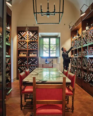 Man in a suit placing a wine bottle onto a floor-to-ceiling wine display in a wine cellar