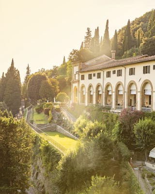 Hilltop monastery hotel amid cypress trees and lush gardens