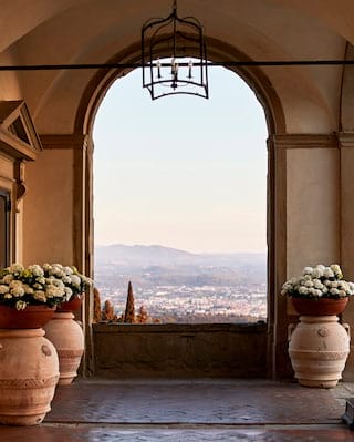 White hydrangeas in grecian pots beside a stone arch framing a view of Florence