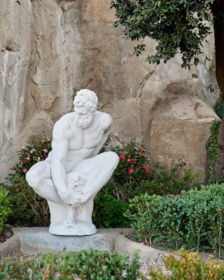 Close-up of a Jupiter statuette among lush shrubs and red flowers