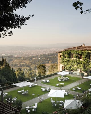Aerial view of garden chairs and tables dotted across a lawn with Florence views