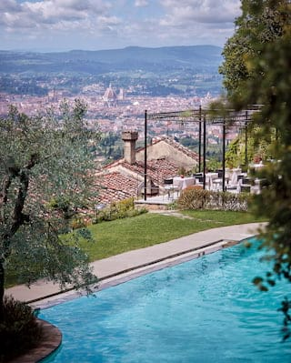 Aerial view of an outdoor pool on a hilltop overlooking the city of Florence