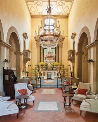 Guest lounge area in a former chapel, lined with plush armchairs and coffee tables