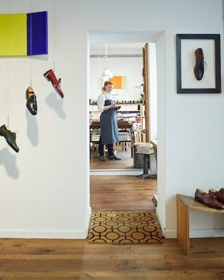 Bright museum-style shoemaker's workshop with a wall display of leather shoes