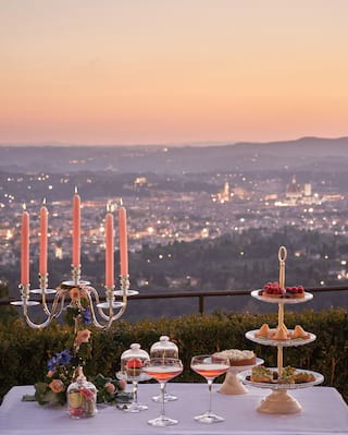 Two cosmopolitan cocktails and a tiered dessert stand on a table with Florence views