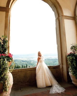 Bride in a wedding dress leaning against a stone arch with views of the hills of Fiesole