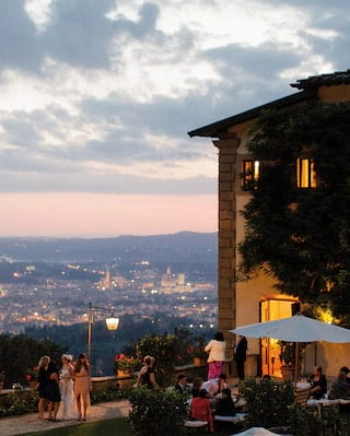 Guests celebrating in the lantern lit gardens of a hilltop hotel at sunset