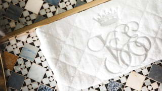 Bathmat embroidered with 'VSOE' placed against multicoloured mosaic tiles
