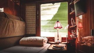 Cosy bed in a lamplit train cabin suite with views through a large window beyond
