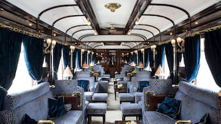 Train bar car with blue velvet banquette seating and blush coloured table lamps